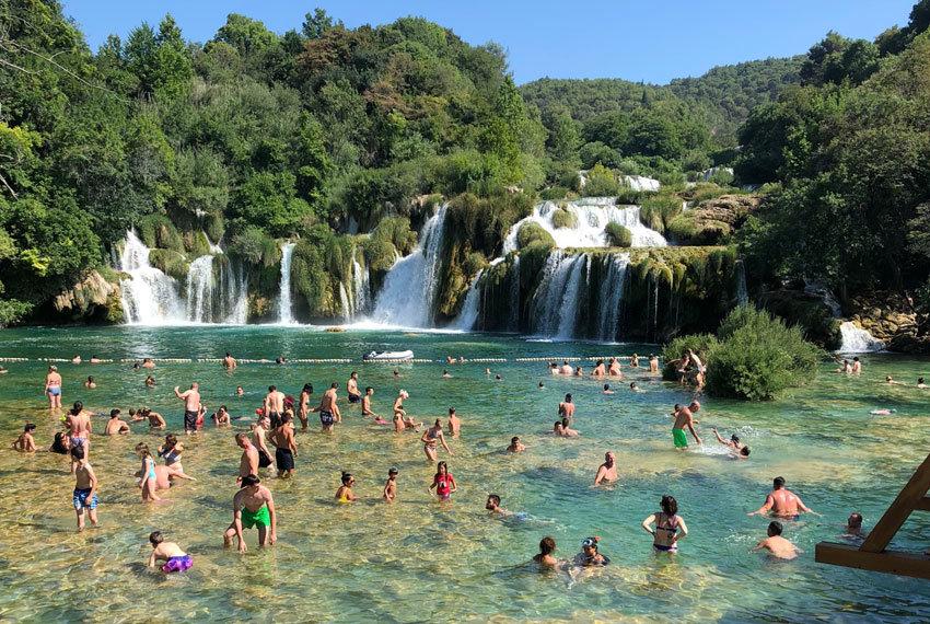Badende Menschen vor dem Skradinski Buk Wasserfall mit klarem Wasser und grüner Umgebung.