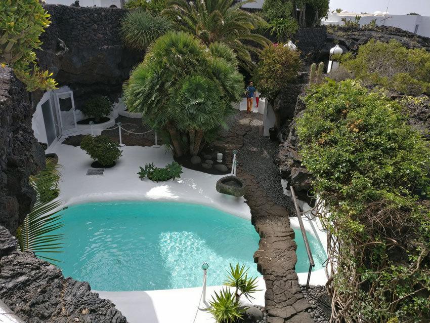 Der Gartenbereich mit Pool, Lavagestein und Palmen in Manriques Haus.