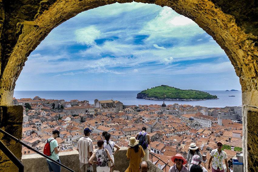 Blick durch einen steinernen Torbogen auf die Stadt und einen Felsen im Meer. Rouristen sind von weitem zu sehen