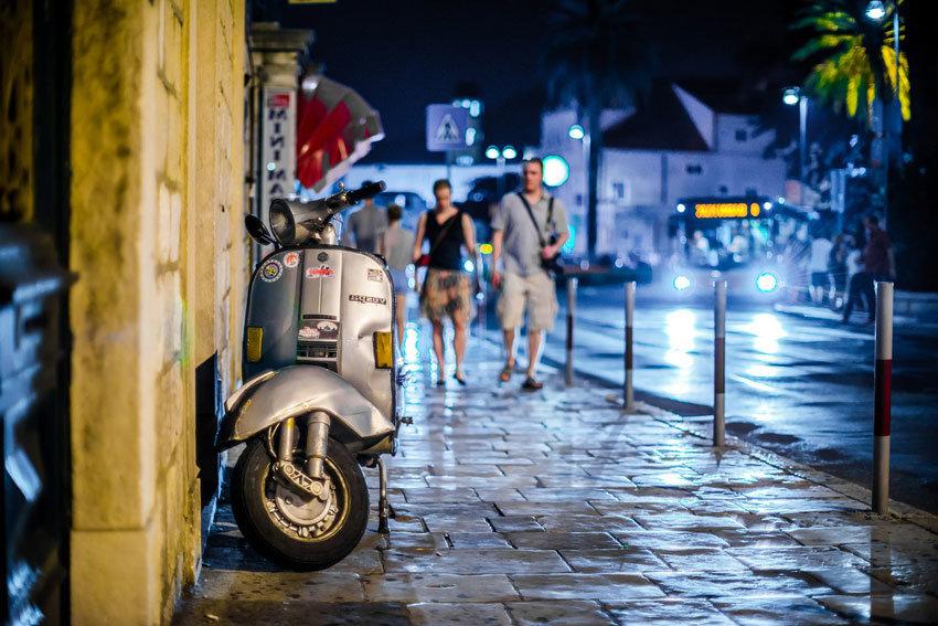 Straße mit zwei Männern im Hintergrund bei Nacht und einem Motorrad, das an die Wand gelehnt ist.