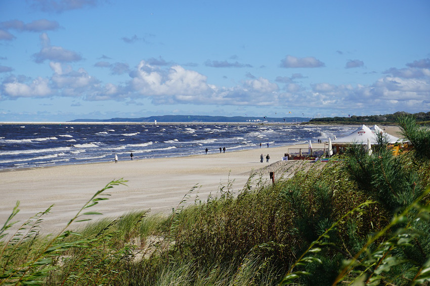 Sandstrand an der Ostsee mit leicht bewölktem Himmel und Gräsern im Vordergrund